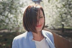 La bella ragazza castana sorridente con i capelli di scarsità in un cappotto blu dell'estate è in un giardino fiorito della molla fotografia stock libera da diritti