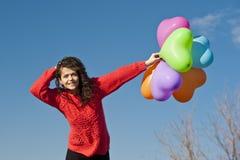 La bella ragazza caucasica con un mazzo di cuore balloons sui precedenti blu dello sci Fotografia Stock
