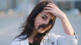 La bella ragazza caucasica giovanile con capelli marroni lunghi che cammina in avanti alla macchina fotografica accarezza la suoi video d archivio