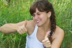 La bella ragazza charming mostra i pollici in su Immagine Stock
