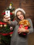 La bella ragazza che fa i selfies si avvicina all'albero del nuovo anno Fotografie Stock