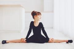 La bella ragazza che fa l'allungamento si esercita alla scuola di balletto Immagine Stock Libera da Diritti