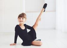 La bella ragazza che fa l'allungamento si esercita alla scuola di balletto Immagini Stock