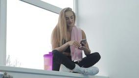 La bella ragazza che fa l'esercizio nella ragazza gymbeautiful intelligente fa il selfie su un telefono cellulare mentre si siede