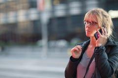 La bella ragazza che parla sul telefono alla notte su una via occupata della città che sembra preplexed e si stanca Immagine Stock Libera da Diritti