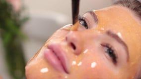 La bella ragazza che riposa e fa una maschera dell'oro in un salone di bellezza video d archivio