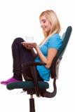 La bella ragazza che si rilassa nella sedia tiene una tazza di tè o di caffè Fotografie Stock Libere da Diritti