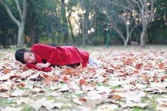 La bella ragazza che si rilassa sul giallo lascia nel parco di autunno Immagine Stock