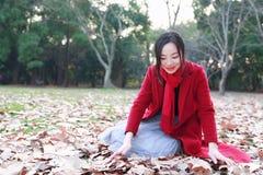 La bella ragazza che si rilassa sul giallo lascia nel parco di autunno Fotografie Stock Libere da Diritti