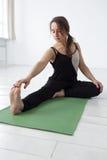 La bella ragazza che si siede nel asana di yoga, prepara per Janu Sirsasana immagini stock libere da diritti
