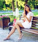 La bella ragazza che si siede su un banco, castana in vestito rosa, stile di vita di modo con il vostro telefono scrive il social Immagini Stock Libere da Diritti