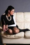 La bella ragazza che si siede su una base fotografia stock