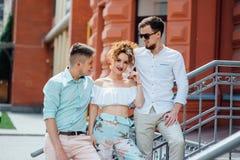 La bella ragazza comunica con due tipi alla moda fotografie stock libere da diritti