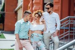 La bella ragazza comunica con due tipi alla moda fotografie stock