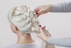La bella ragazza con capelli biondi, parrucchiere tesse un primo piano della treccia immagine stock