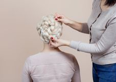 La bella ragazza con capelli biondi, parrucchiere tesse un primo piano della treccia, in un salone di bellezza fotografia stock libera da diritti