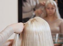 La bella ragazza con capelli biondi, parrucchiere tesse un primo piano della treccia, in un salone di bellezza immagine stock