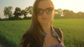 La bella ragazza con capelli lunghi diritti si sviluppa nel vento, stante nel campo al tramonto stock footage