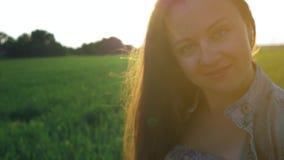 La bella ragazza con capelli lunghi diritti si sviluppa nel vento, stante nel campo al tramonto archivi video