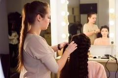 La bella ragazza con capelli lunghi, parrucchiere tesse una treccia francese, in un salone di bellezza Cura e creare di capelli p fotografie stock libere da diritti