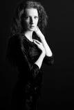 La bella ragazza con capelli ricci ed il vestito nero Fotografia Stock