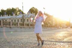 La bella ragazza con capelli rosa in un vestito blu dall'estate cammina intorno alla città all'alba con un vetro in sua mano immagine stock