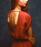 La bella ragazza con capelli rossi in aperto sexy indietro si veste Fotografie Stock