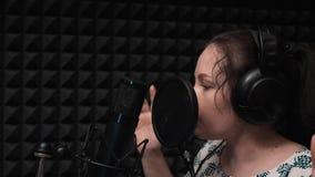 La bella ragazza con gli occhi azzurri in cuffie canta vicino al microfono nella sala di registrazione Audio registrazione Canto  stock footage