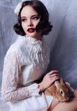 La bella ragazza con i capelli di scarsità scuri indossa i retro vestiti Fotografia Stock