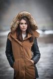 La bella ragazza con il cappotto marrone ha sistemato con pelliccia grigia che gode del paesaggio dell'inverno in parco Adolescen fotografie stock libere da diritti