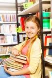 La bella ragazza con il mucchio dei libri si siede vicino allo scaffale Fotografia Stock Libera da Diritti