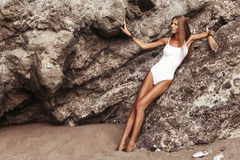 La bella ragazza con l'abbronzatura in costume da bagno si siede sulle rocce alla spiaggia Immagini Stock