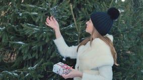 La bella ragazza con le labbra rosse tiene un regalo festivo al fondo dell'abete video d archivio