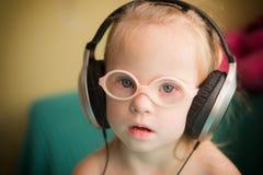 La bella ragazza con sindrome di Down sta ascoltando musica sulle cuffie Immagini Stock