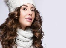 La bella ragazza con trucco delicato, i riccioli ed il sorriso nel bianco tricottano il cappello Immagine calda di inverno Fronte Fotografia Stock Libera da Diritti