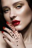 La bella ragazza con trucco di sera, le labbra rosse in cristalli di rocca e la progettazione manicure le unghie Fronte di bellez fotografie stock libere da diritti