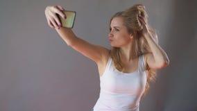 La bella ragazza con trucco leggero prende un selfie su un fondo grigio archivi video