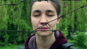 La bella ragazza con un fronte triste, sta dietro filo spinato stock footage