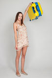 La bella ragazza con una valigia di giallo ama viaggiare Fotografia Stock
