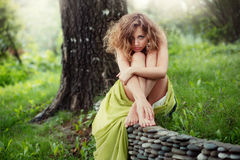 La bella ragazza con uno sguardo sexy si siede sull'erba Fotografie Stock