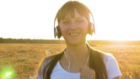 La bella ragazza in cuffie ascolta musica e va dentro per pareggiare ed i sorrisi di sport Sport come stile di vita stock footage