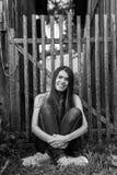 La bella ragazza dai capelli lunghi vicino al di legno recinta il villaggio Fotografia Stock