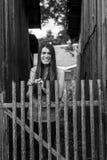 La bella ragazza dai capelli lunghi vicino al di legno recinta il villaggio Immagine Stock Libera da Diritti