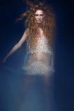 La bella ragazza dai capelli rossi alla moda in vestito trasparente, immagine della sirena con l'acconciatura creativa arriccia S fotografia stock libera da diritti