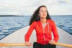 La bella ragazza dai capelli stupefacente nuota su una barca e su una rematura di legno con i remi nel lago splendido della molla Immagini Stock