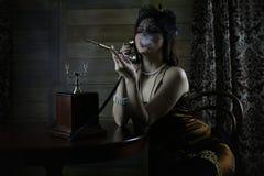 La bella ragazza degli anni 30 fuma fotografia stock libera da diritti