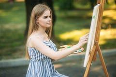 La bella ragazza dei capelli biondi che si siede sulle feci e disegna un'immagine nel parco facendo uso di una tavolozza con le p immagini stock