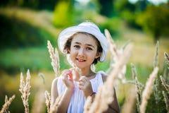 La bella ragazza del bambino con capelli biondi lunghi viaggia nel campo giallo variopinto Immagini Stock Libere da Diritti
