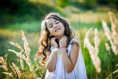 La bella ragazza del bambino con capelli biondi lunghi viaggia nel campo giallo variopinto Immagini Stock
