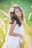 La bella ragazza del bambino con capelli biondi lunghi viaggia nel campo giallo variopinto Fotografia Stock